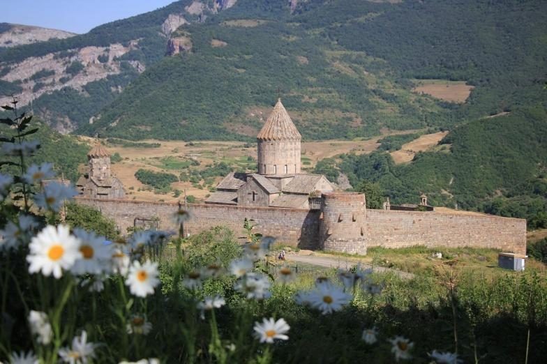 A stone monastery on a plateau with daisies in the foreground.