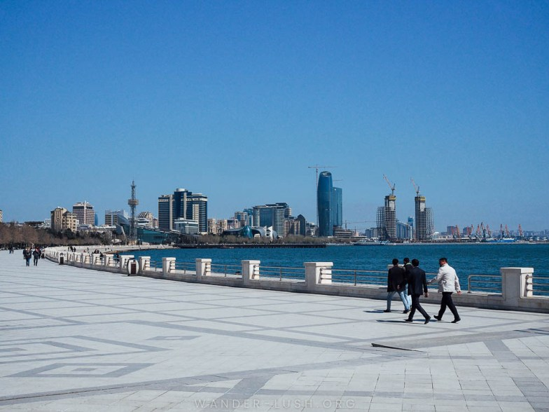 A group of men in suits walk along the grey sidewalk along the Caspian Sea in Baku.
