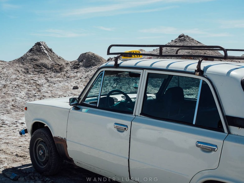A white taxi sits in a landscape of grey mud volcanoes.