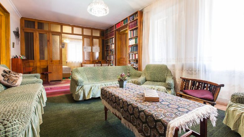 A comfortable living room at an accommodation in Georgia, with green couches.
