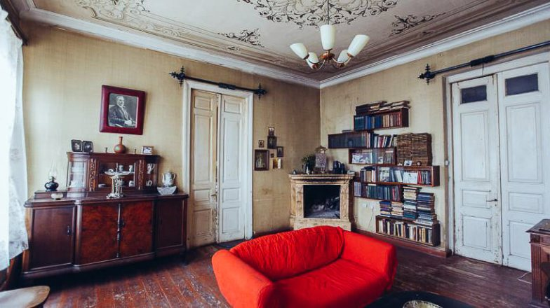 A room with weathered wooden floors and a red sofa in the centre.