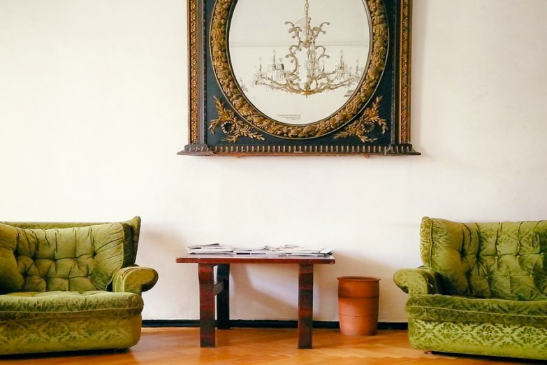 Two matching green couches on a wooden floor with a large mirror and chandelier in between them.
