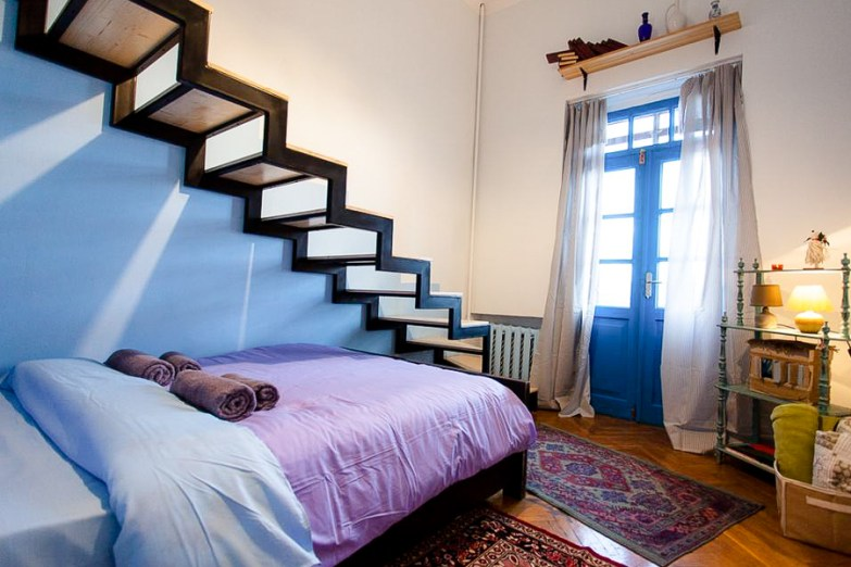 A homely bedroom with a bed, floor rugs, and a blue door.