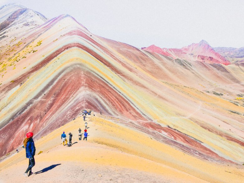 A group of trekkers walking along a ridge in Peru's rainbow mountains.
