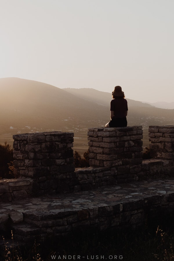 A woman sitting on the ruins of a stone castle at sunset.