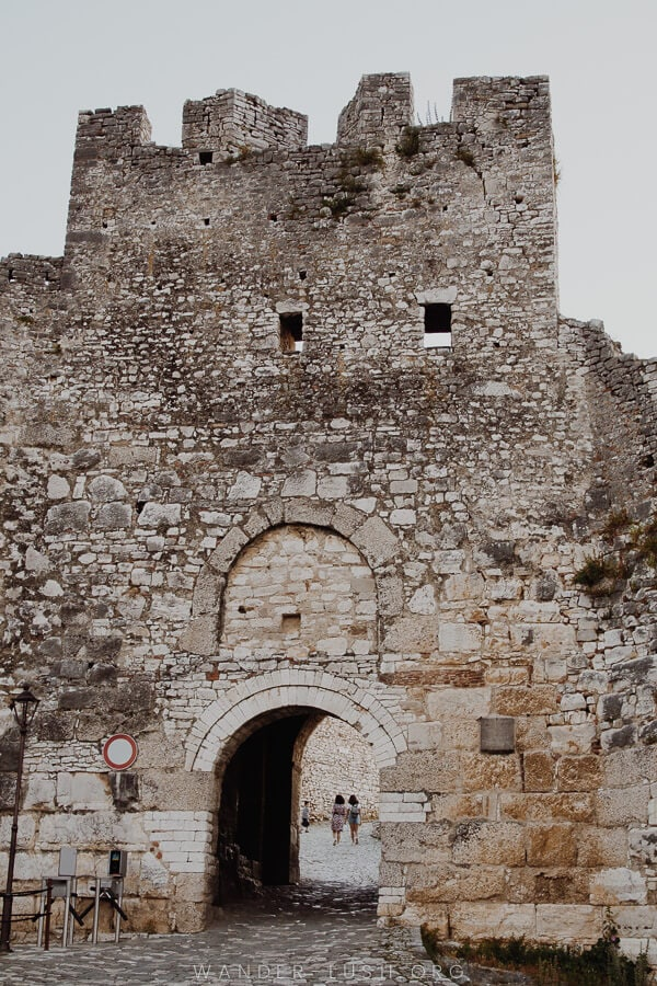 A high stone wall with an entrance portal.
