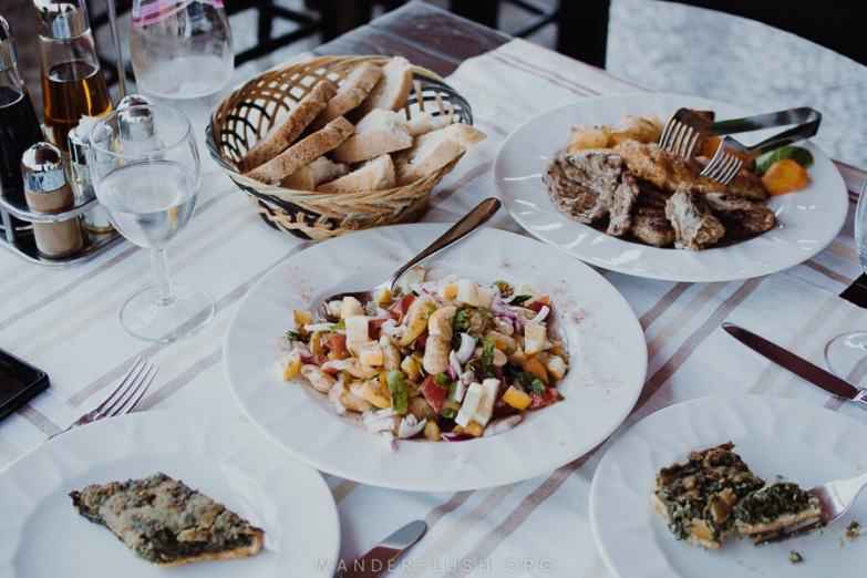 A table set with salad, meat, bread and wine glasses. Eating local cuisine is one of the best things to do in Berat, Albania.