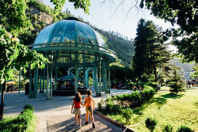 Two kids walking in a leafy park.