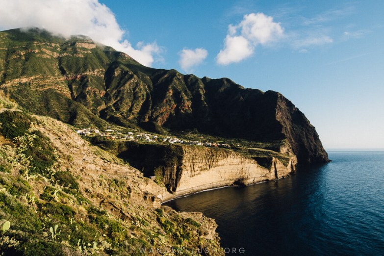 A volcanic crater with a white village in the basin. A beautiful view of Pollara on Salina Island in the Aeolian Islands.