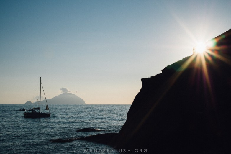 A boat on the sea and a starburst shining through a dark rock formation.