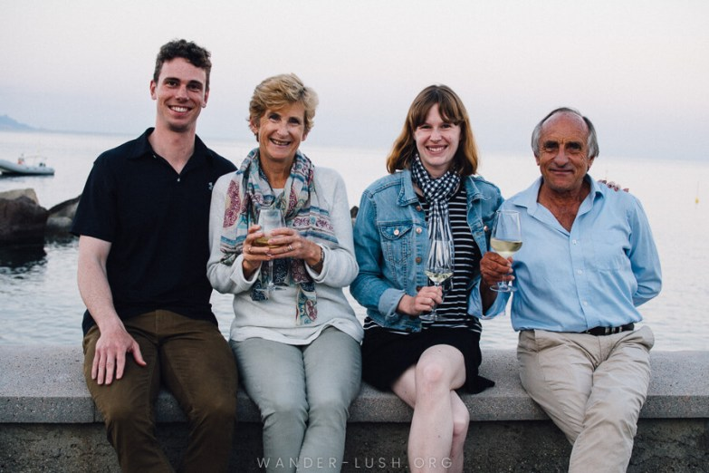 Two women and two men sitting on a concrete wall with the Aeolian Islands in the background.