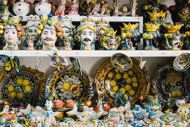 Colourful ceramics on a white shelf.