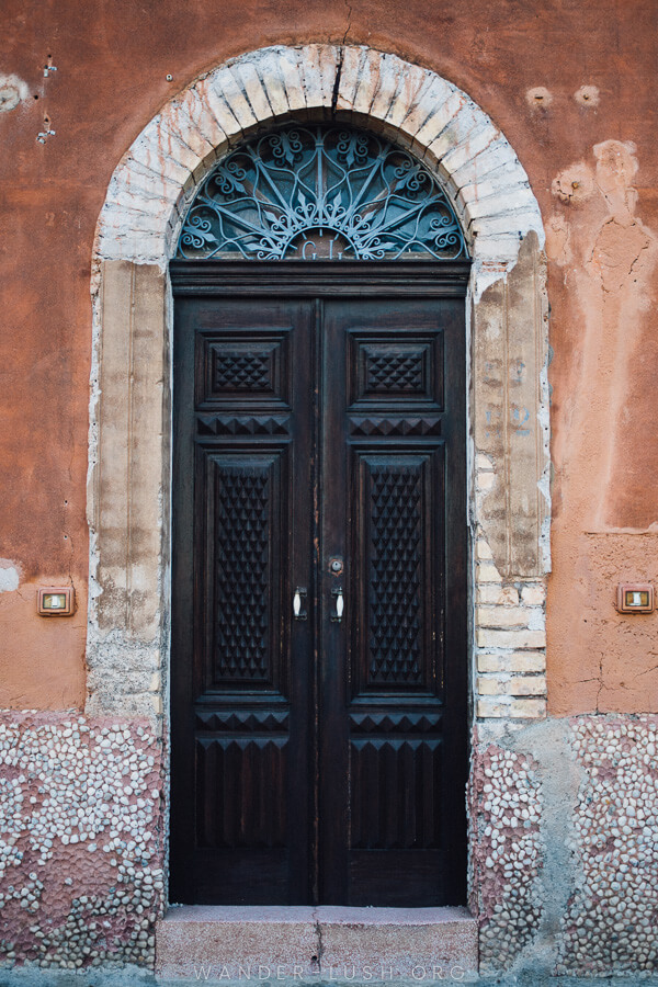 A beautiful wooden door with an arched window.