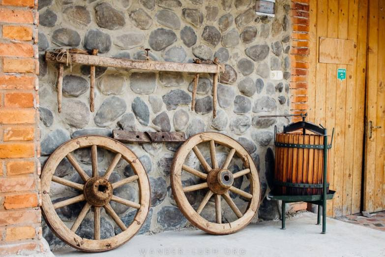 Old wooden wheels propped up against a brick building at Baia's Wine.