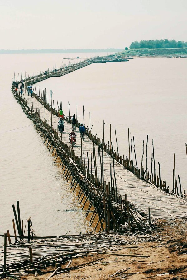 A long bamboo bridge over a river trails off into the distance.