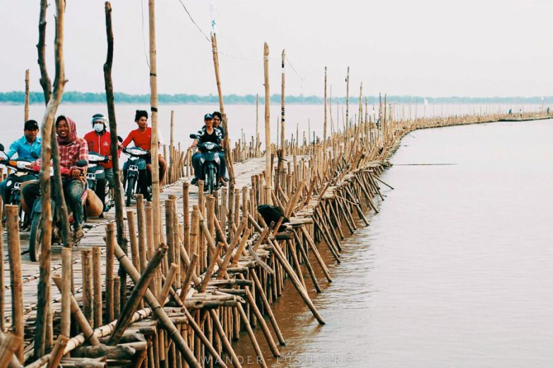 Five men ride motorcycles across a long bamboo bridge over a light brown river.