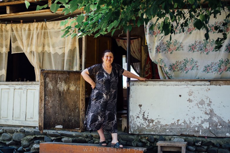 A woman stands in front of her home in Pankisi Gorge.