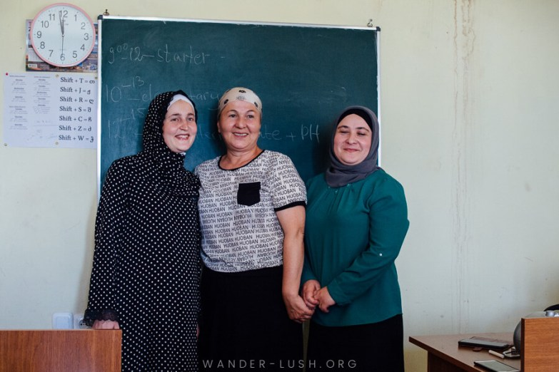 Three women teachers pose for a photo in front of their blackboard.