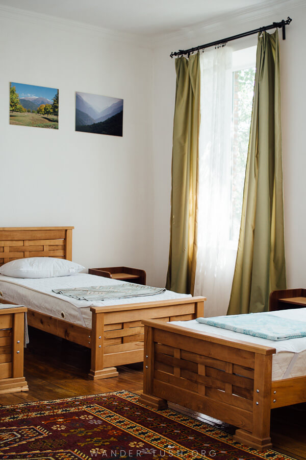 Three wooden beds in a light-filled bedroom.