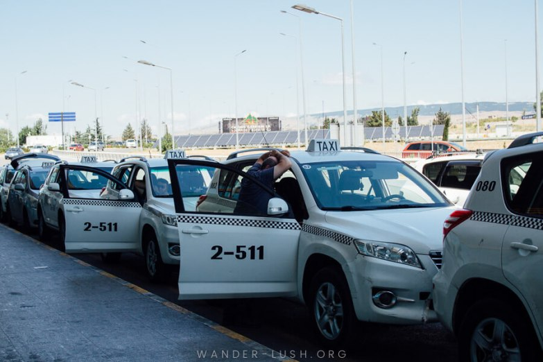A row of white taxis waiting outside Tbilisi Airport.