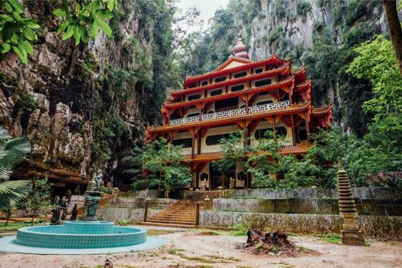 A red and white temple built into the side of a limestone cliff.