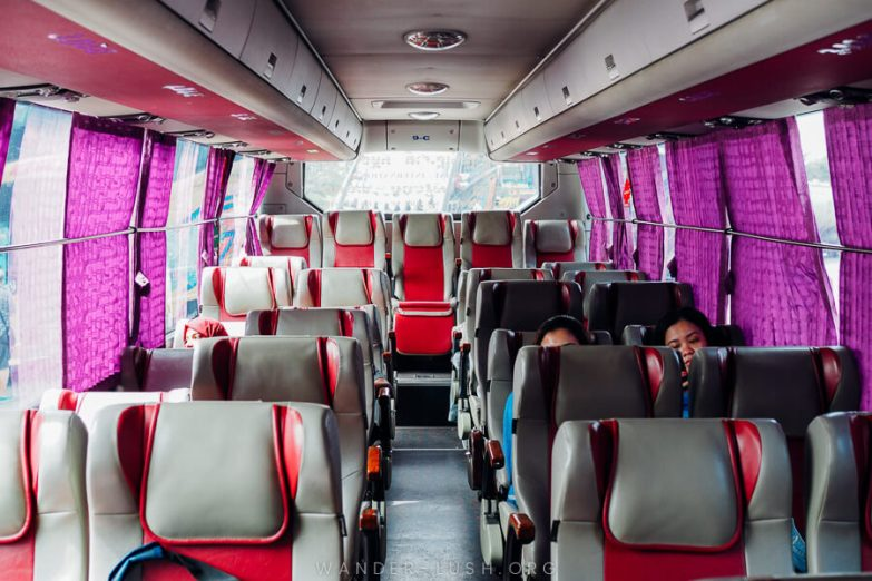 The interior of a bus with red and grey seats and purple window curtains.
