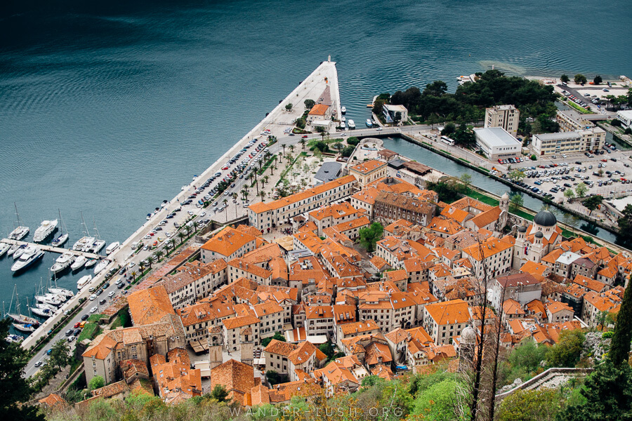 A triangle-shaped bay and an old town made up of hundreds of orange roofs viewed from above.