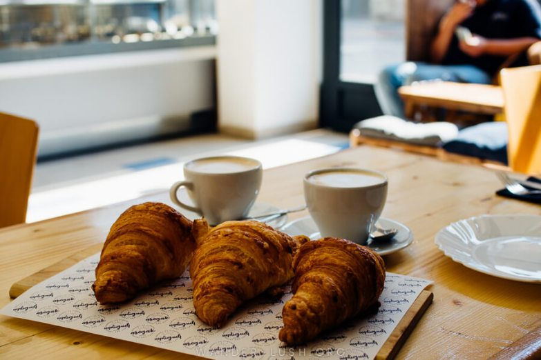 Three croissants and two cups of coffee on a wooden table at a cafe in Gyumri.