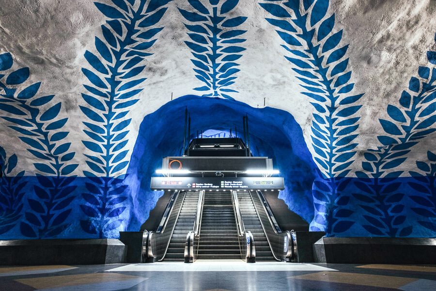 A metro station in Stockholm decorated with blue and white paintings on the ceiling.