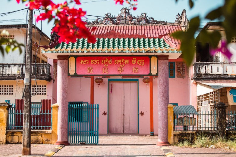 A pink building with a colourful roof and Chinese script above the door.