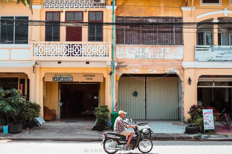 A man rides a motorbike past a row of yellow and white shophouses in Kampot, Cambodia.