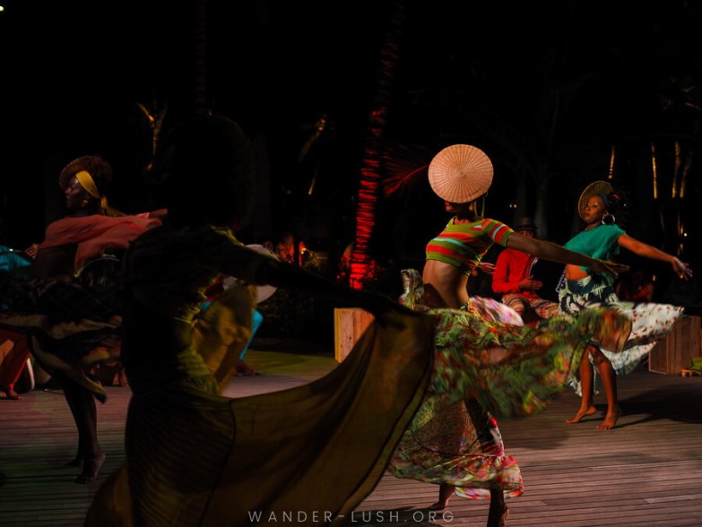 Four women dressed in long flowing skirts perform a traditional Mauritian culture dance.