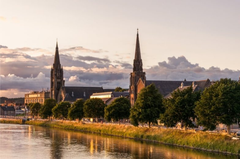 Church spires at dusk in a glimmering waterfront city.