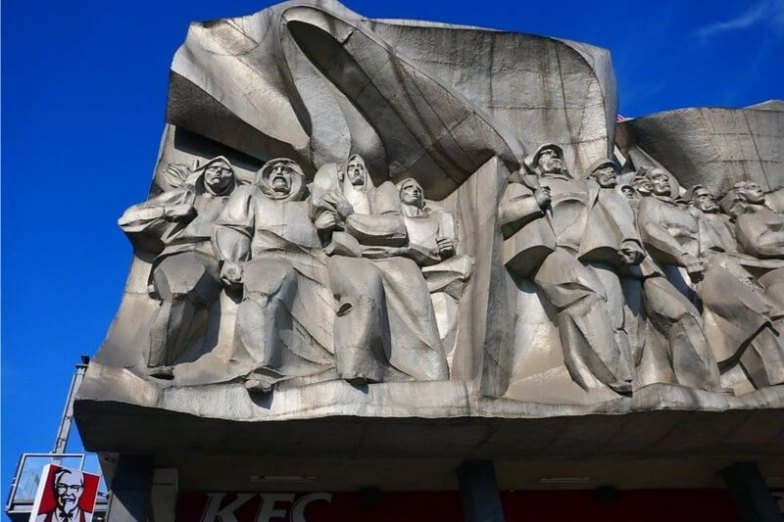 A grey sculpture sitting on top of a KFC restaurant.
