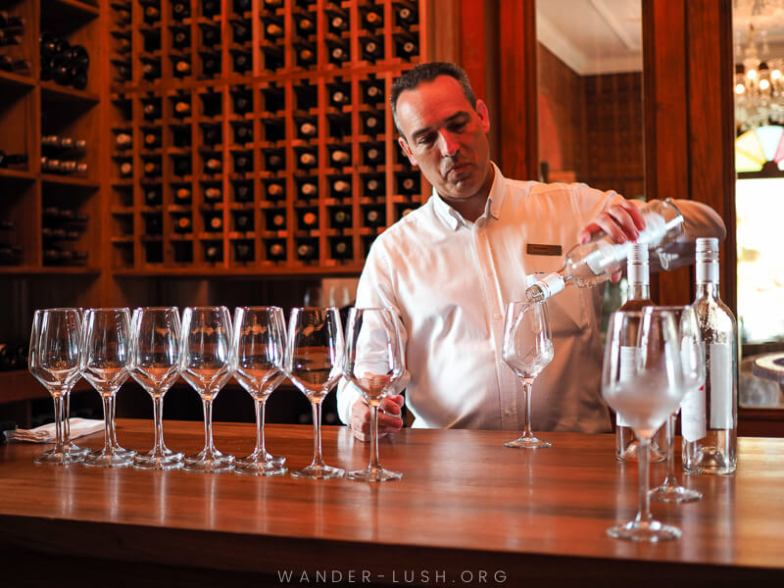 A man in a white dress shirt pours white wine into a glass.