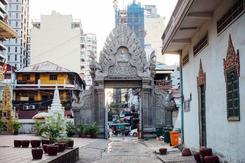 A grey concrete archway engraved with Buddhist symbols marks the entry to a wat in Phnom Penh.