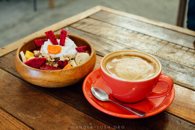 A cup of coffee and a bowl of muesli with yogurt and fruit on top.
