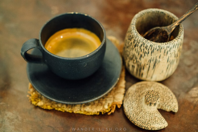A small black cup of espresso coffee and a wooden sugar pot.