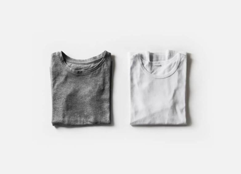Two folded t-shirts, one grey and one white.