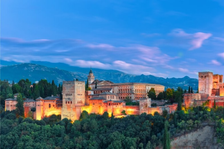 The Alhambra at night, emerging from a forest of green trees against an inky blue sky.