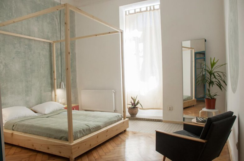 A modern room with a four-poster bed and polished wood floors.