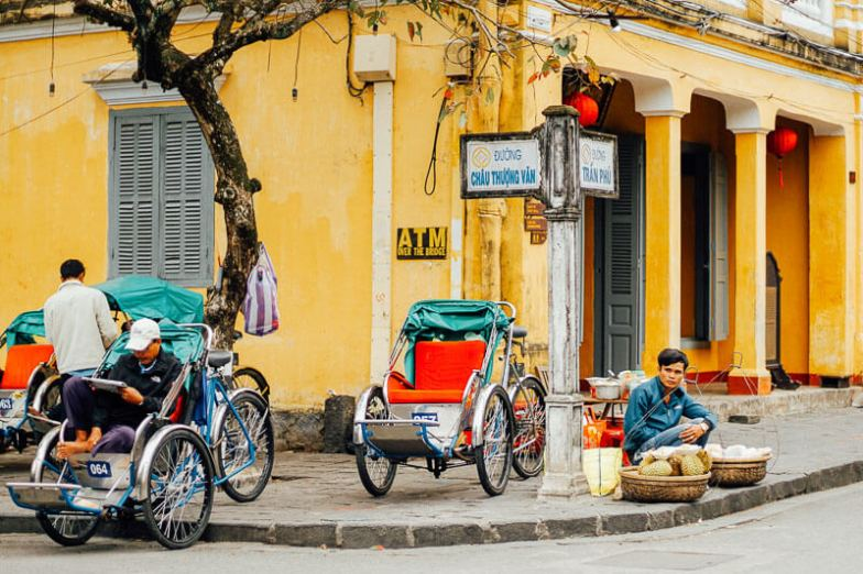 Yellow buildings and cyclos in Hoi An Ancient City.