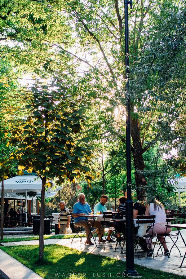 People sit in a leafy beer garden in Korca.