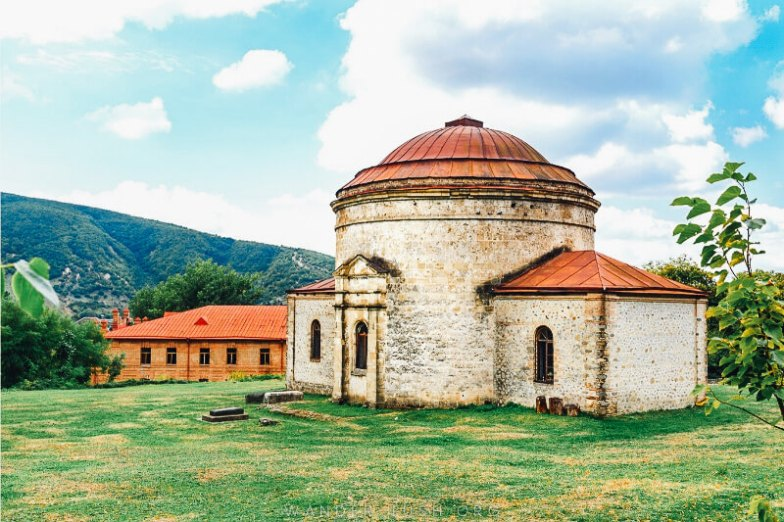 A rounded church made from stone in the middle of a grassy field.