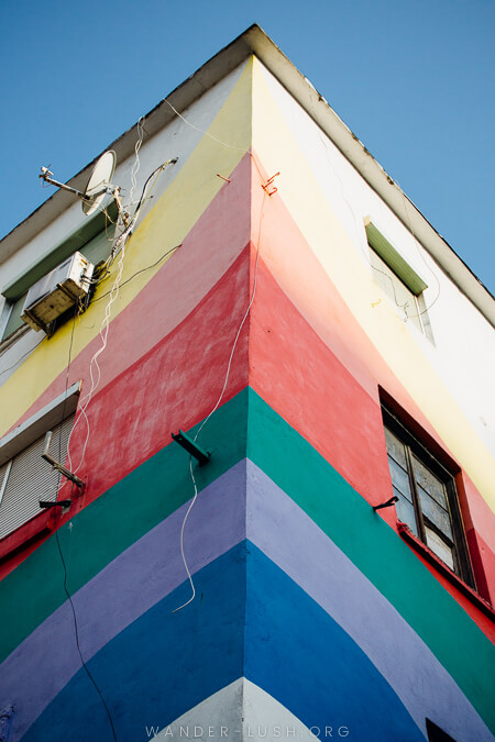 A corner building painted to resemble a rainbow.