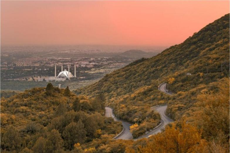 A red sky at dusk with a mosque visible in the valley.