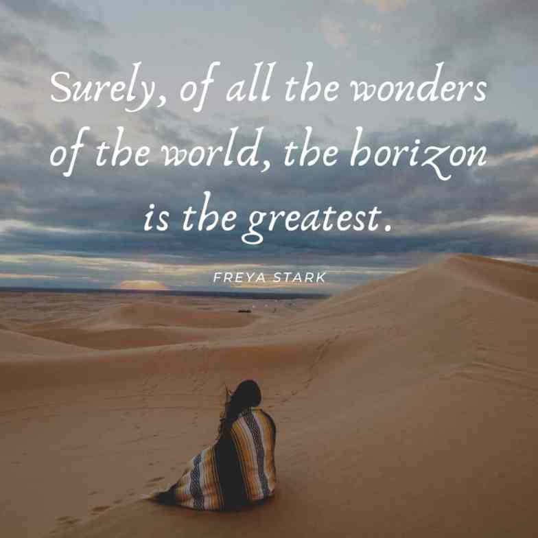 A woman wrapped in a blanket sits on a sand dune and looks out to the horizon.