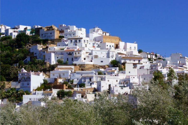 White buildings cling to a hillside in Spain.
