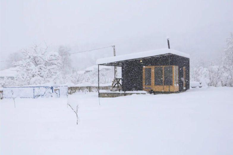 A small cabin in Georgia on a snowy field.