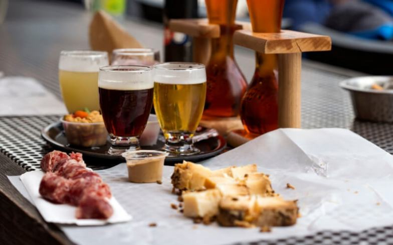 A table spread with sausage and glasses of Belgian beer.